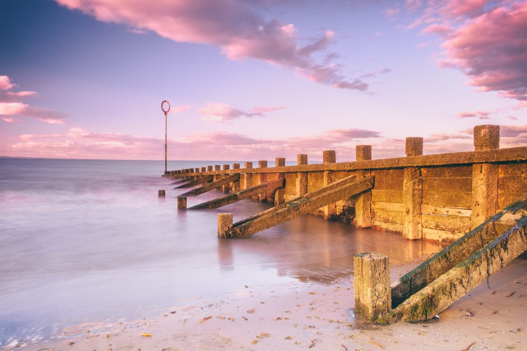 Sunset view of Edinburgh's Portobello Beach with wooden groynes. Scotland, United Kingdom