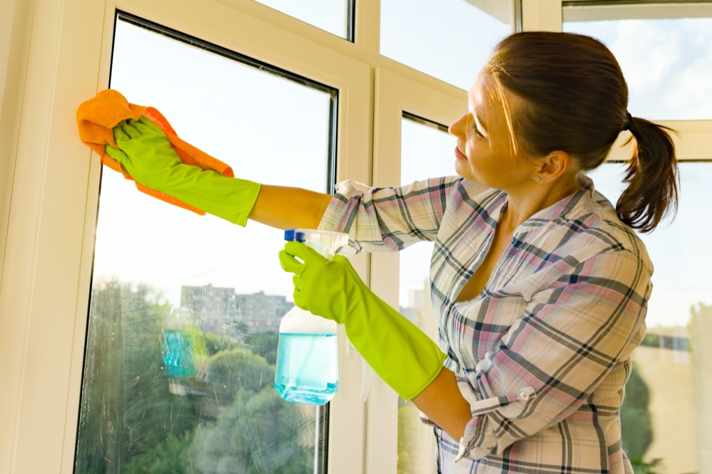 Close-up of woman cleaning windows, hands in rubber protective gloves, rag and sprayer detergent
